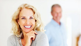 Joyful mature woman smiling while blur man in background